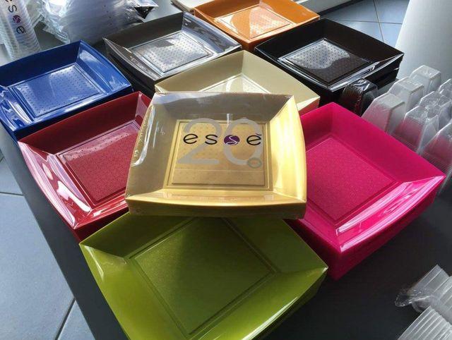 serie di contenitori in plastica quadrati di color verde, rosso,blu, grigio, beige,rosa,nero e arancione e sopra questi uno confezionato di color giallo
