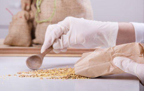 Due mani con un guanto spargono dei semi su un tavolo