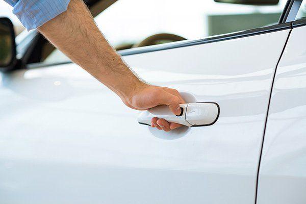 mano che apre la portiera di un'auto