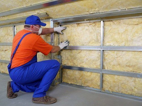 Operaio che monta rivestimento isolante per le pareti