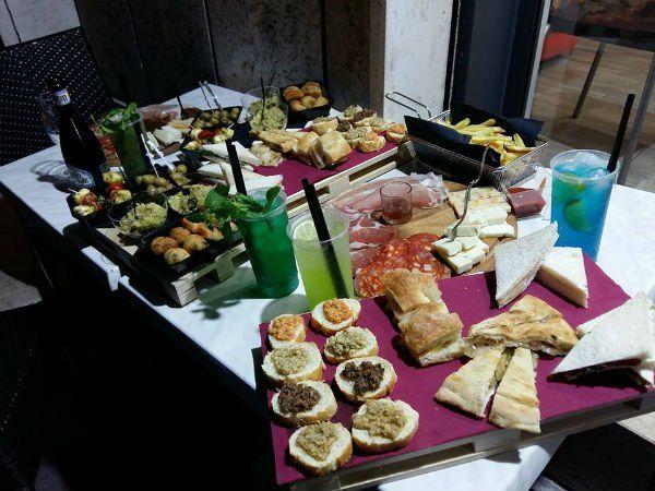 un buffet con degli antipasti, tramezzini e dei cocktail