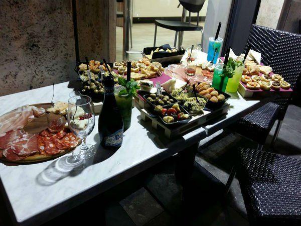 un tavolo con un tagliere di salumi e altri antipasti