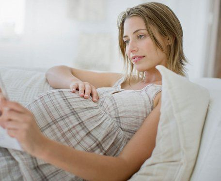 A heavily pregnant young lady in a cream checked dress, relaxing on a white sofa