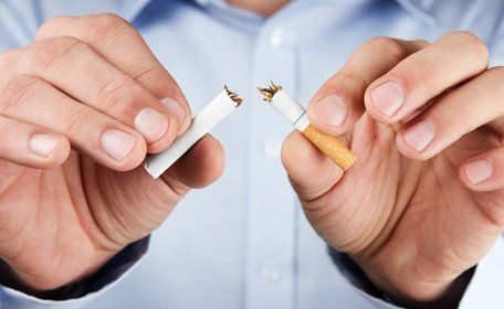 A man snapping a cigarette in half