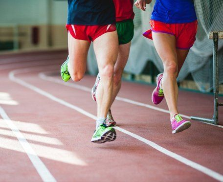 Runners in shorts on an indoor track