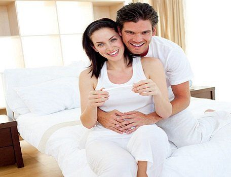 A man sitting on a bed behind his pregnant wife, with his hands on her tummy