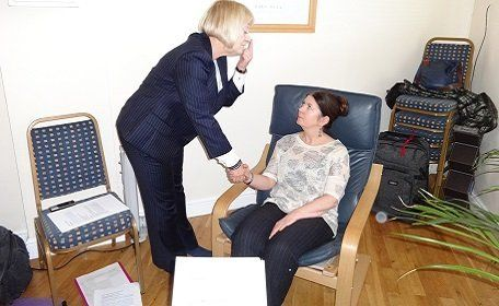 Therapist holding the hand of a lady sitting in a chair