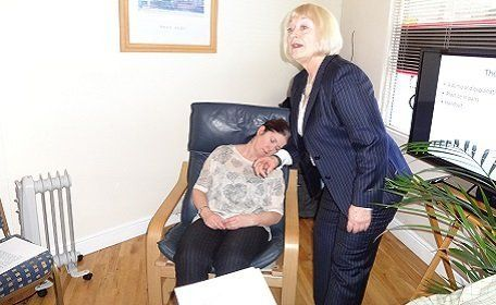 Therapist standing beside a lady asleep in the hypnotherapy session