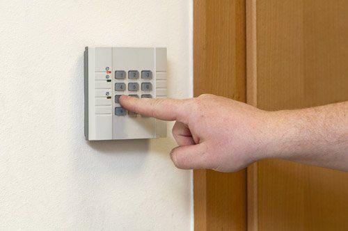 Una mano preme il bottone di una pulsantiera di un antifurto