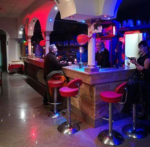 bancone di un bar con i clienti che degustano cocktails