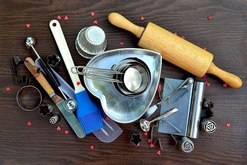 degli stampini per i biscotti, misurini, un martello e altri accessori di una pasticceria