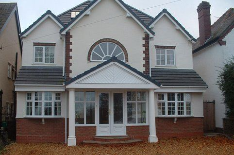A house with white stone pillars on either side of the front doorstep, cream cladding and bay windows