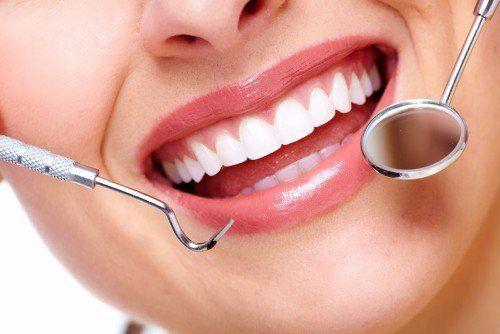 una bocca che sorride e degli strumenti odontoiatrici