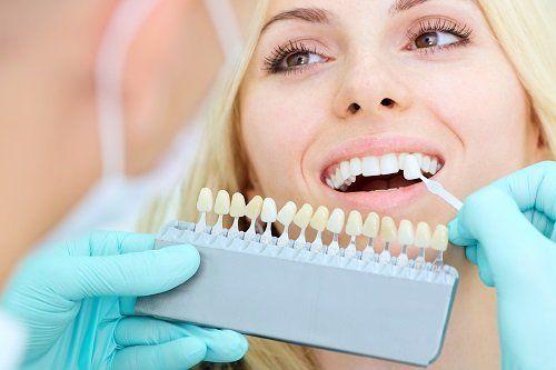 una donna da un dentista che prova dei denti artificiali