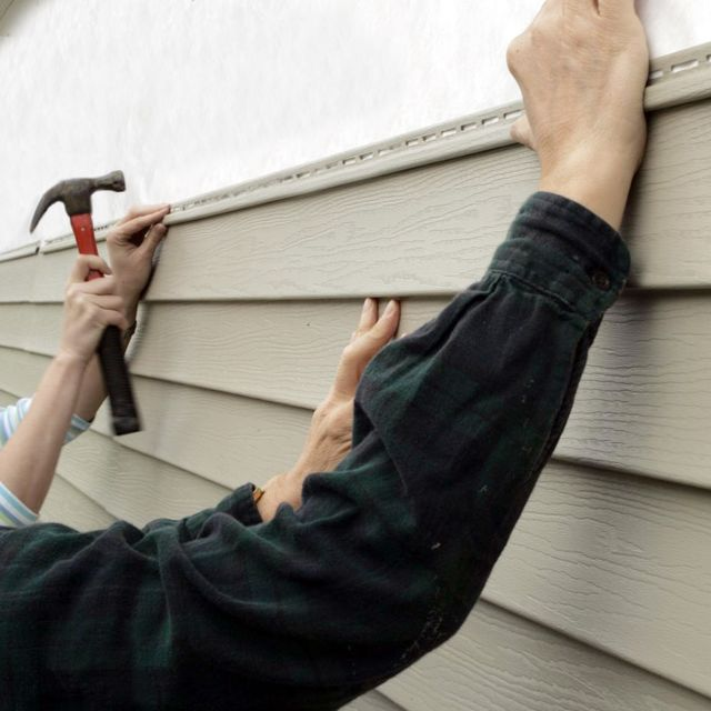 Two workers adding siding to a home