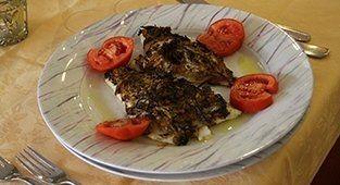 Pesce alla griglia con aglio e fette di pomodoro fresco