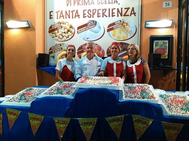 un uomo con un'uniforme bianca e tre donne con con un grembiule rosso uno dietro a un esposizione di torte durante un evento