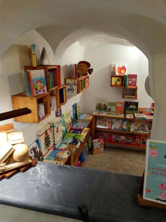 un'antica libreria con muri in pietra e scaffali con dei libri