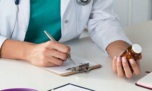 Primo piano di una dottoressa che sta scrivendo su un foglio