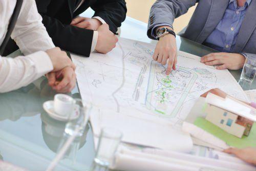 tre uomini si confrontano su un progetto disegnato