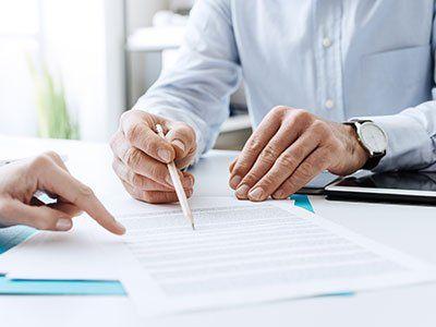 due mani con una matita, mentre sottolineano un documento su di una scrivania
