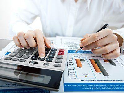 due mani di donna che fanno dei conti su di una calcolatrice