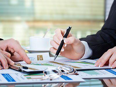 due mani di donna con una penna mentre controllano dei documenti su di una scrivania