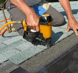 Carpenter using nail gun to attach asphalt shingles