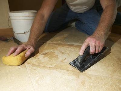 Operaio riempiendo  giunture e pulendo il pavimento