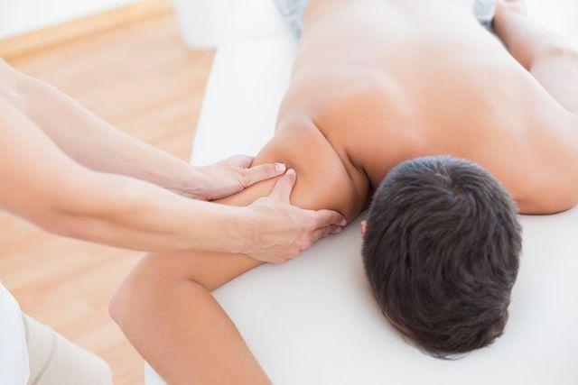Terapista facendo il massaggio sulla spalla del paziente