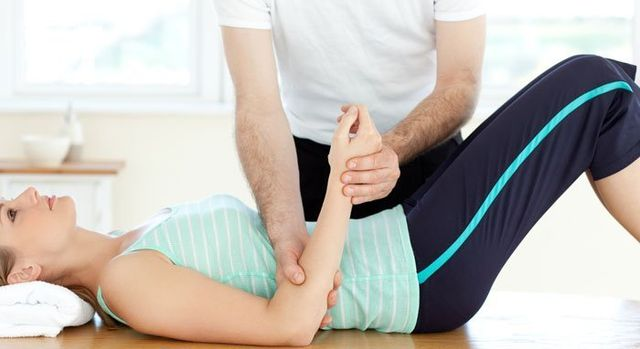 Fisioterapista lavorando nel braccio di una donna