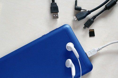 uno smartphone in carica, delle cuffie, una sd card e dei cavi USB
