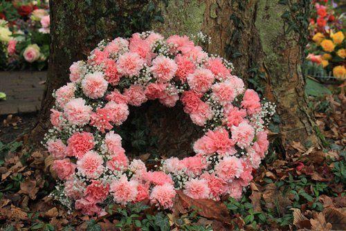 corona di fiori rosa appoggiata su un tronco