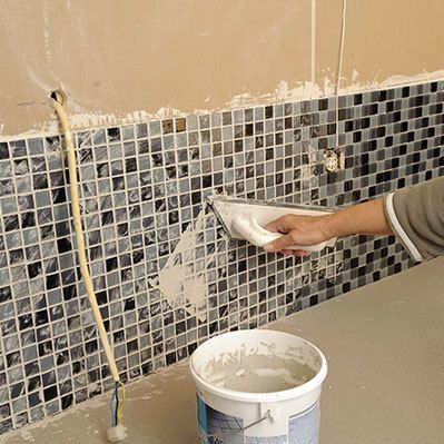 Man tiling the wall in a bathroom for a remarkable remodeling job in Lakeville