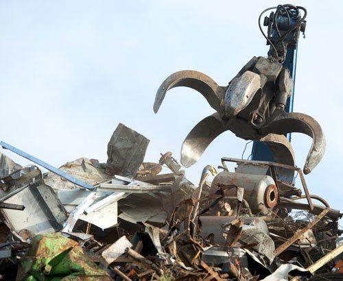 Insieme di rottami metallici e sopra un ragno meccanico che li distrugge