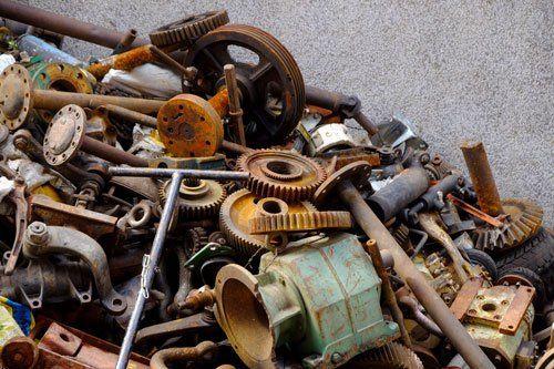 insieme di rottami metallici e ingranaggi, alcuni arrugginiti