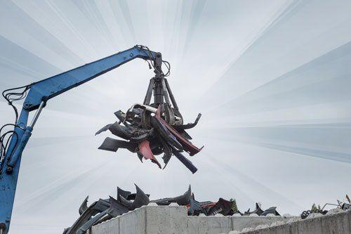 ragno meccanico sta demolendo dei ferri e sotto un ammasso di rottami metallici