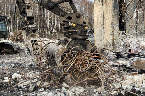 demolitore in un cantiere stringe nella sua morsa del ferro, in lontananza si intravede un veicolo cingolato