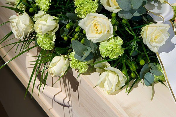 una bara in legno color beige chiaro con un bouquet di rose bianche