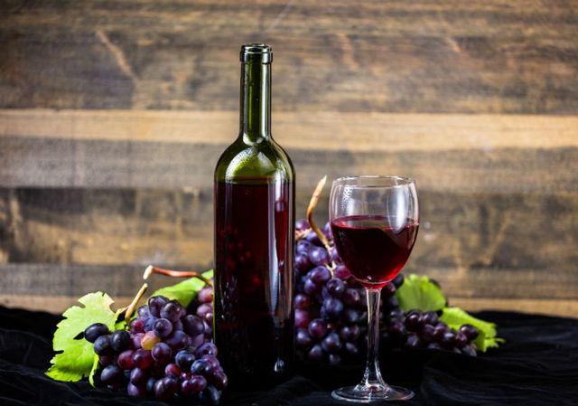 Grappoli di uve nere, bottiglia e bicchiere di vino rosso