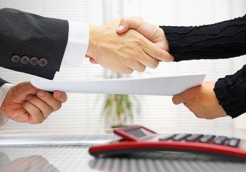 persone che stringono la mano e scambiano un documento