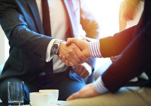 persone con abito formale che si stringono la mano