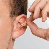 persona si inserisce un apparecchio per l`udito nell`orecchio