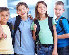 Four school kids wearing rucksacks