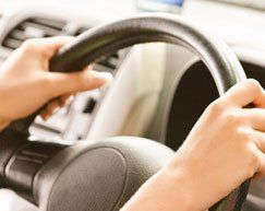 Close up of hands holding a steering wheel