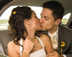 Newly married couple kissing in the back of a car