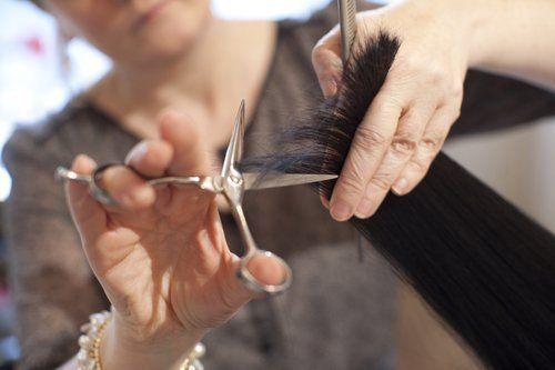 parrucchiera mentre taglia i capelli a una cliente