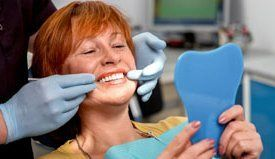 relaxed woman in dental chair with dentist measuring tooth colour brightness