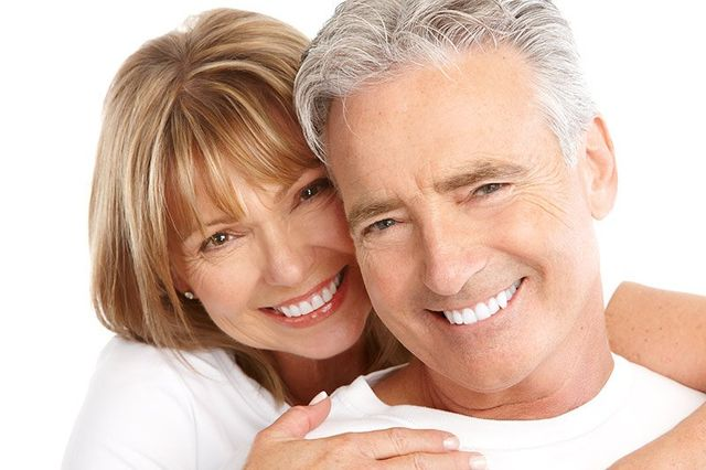 middle aged couple smiling with beautiful teeth