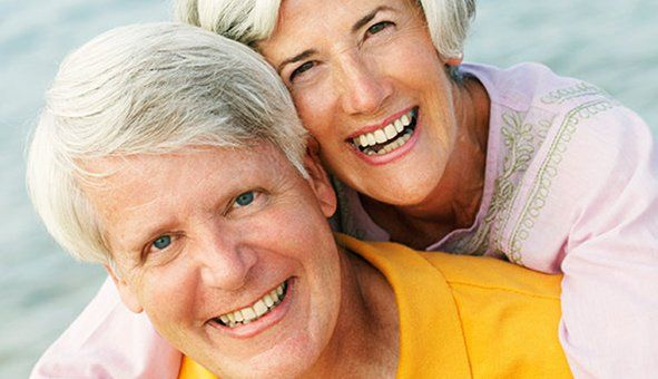 senior couple on the beach smiling with beautiful white teeth